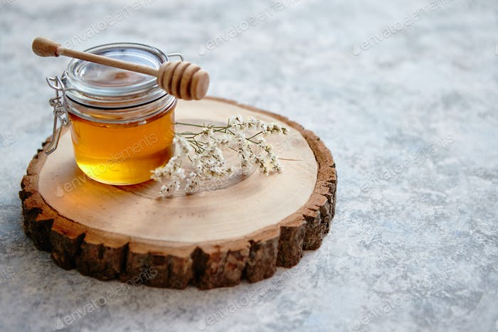 Glass jar full of fresh honey placed on slice of wood