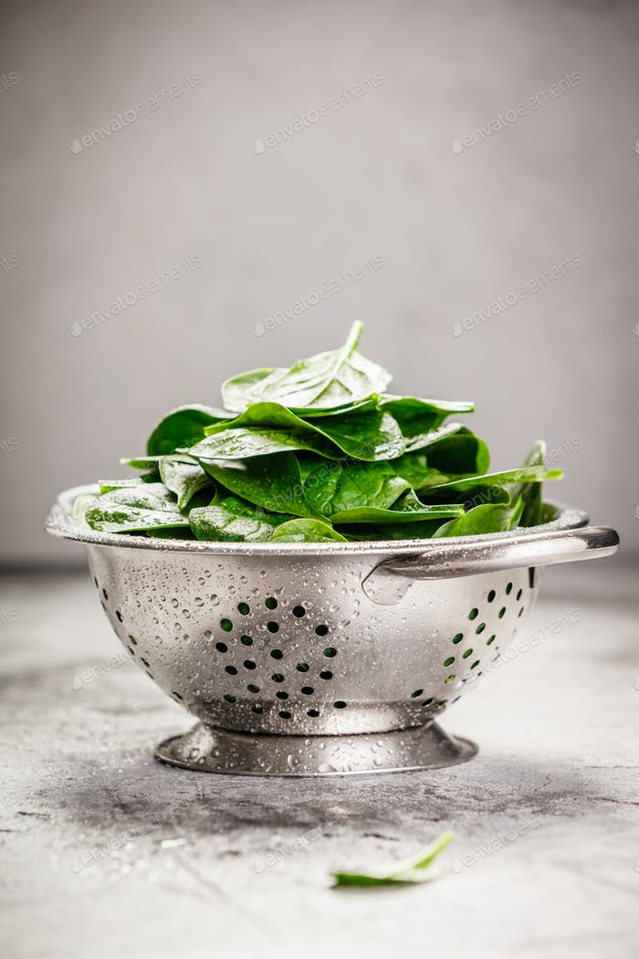 Fresh organic spinach leaves in metal colander