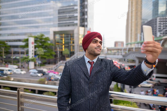 Indian businessman with turban outdoors in city using mobile phone