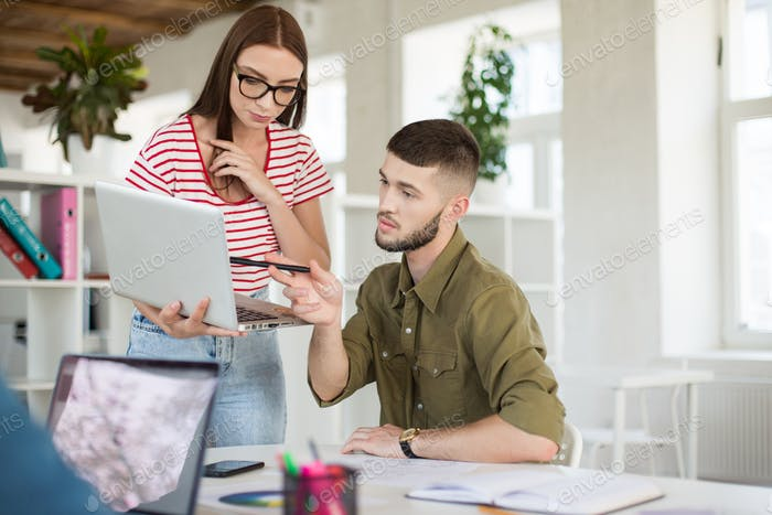 Young business man and woman with laptop working together in mod