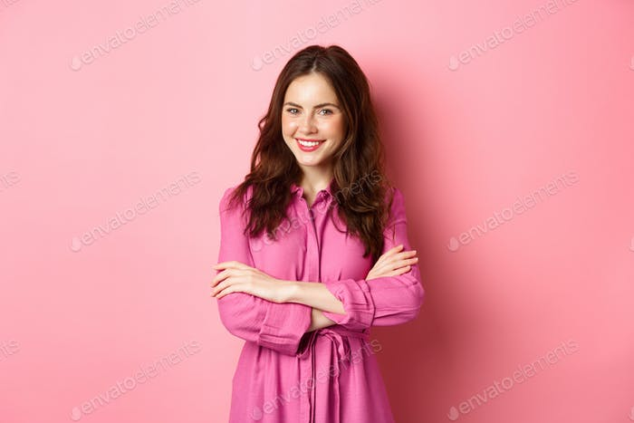 Beautiful feminine woman in spring outfit dress, holding hands crossed on chest and smiling with
