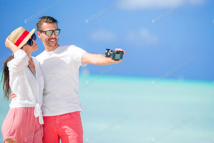 Happy couple taking a selfie photo on white beach. Two adults enjoying their vacation on tropical