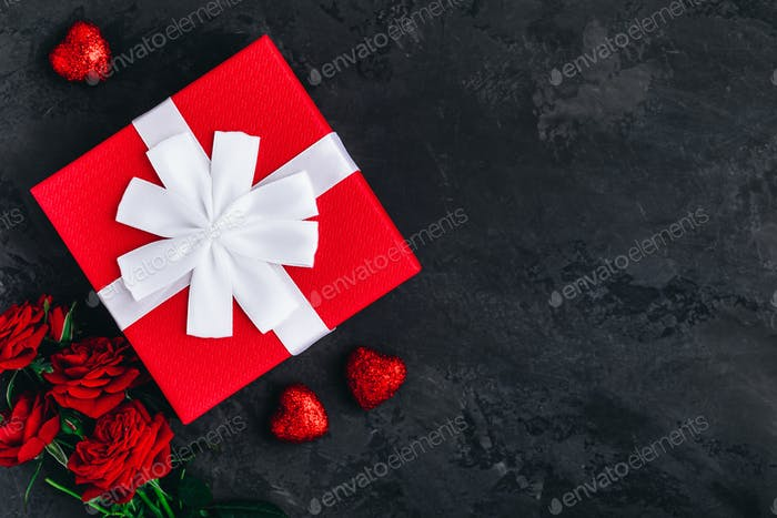 Valentines day background card. Red Gift box and red Roses on dark stone background