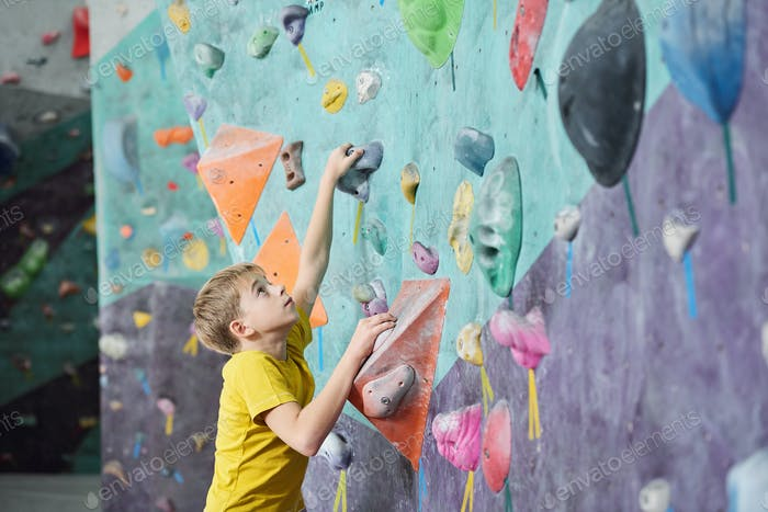 Cute schoolboy in activewear looking upwards while practicing climbing
