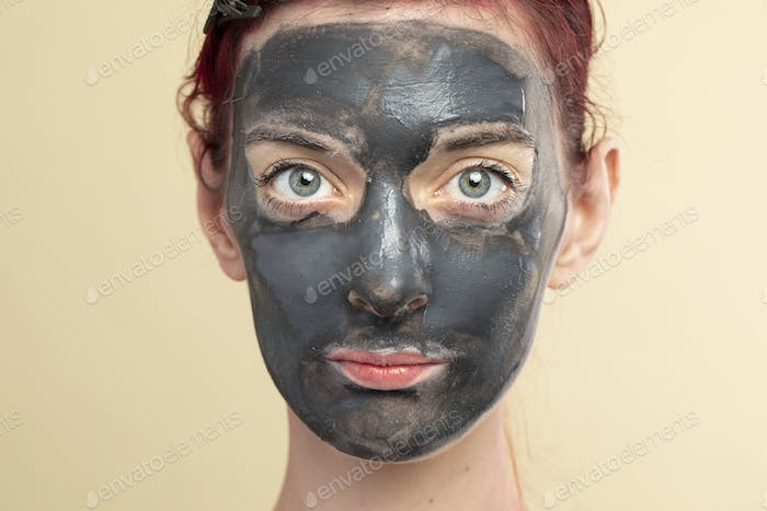 Beautiful woman wearing an activated black charcoal mask for facial treatment