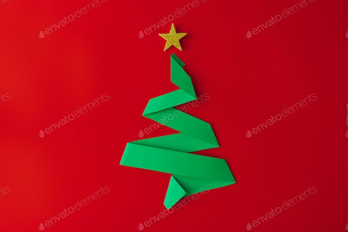 Minimal origami style folded paper christmas tree on red background. Greeting card concept.