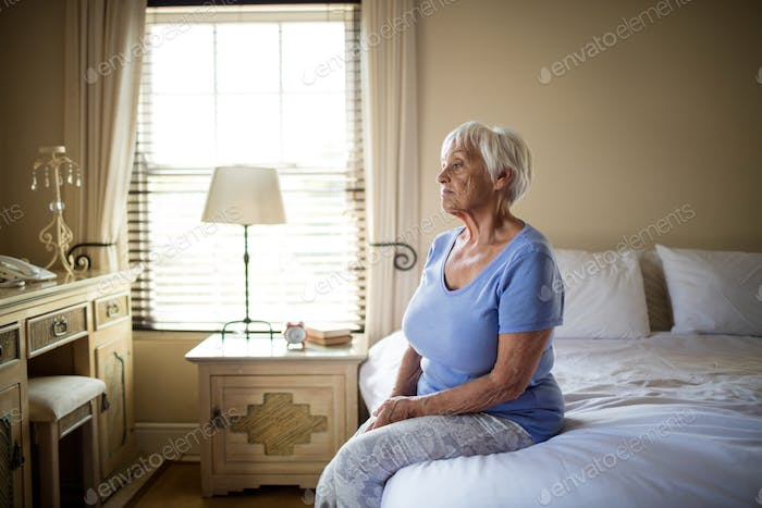 Worried senior woman sitting on bed in the bedroom