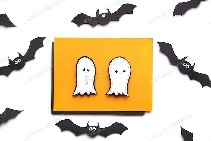 Pair of cute ghosts on orange sheet of paper