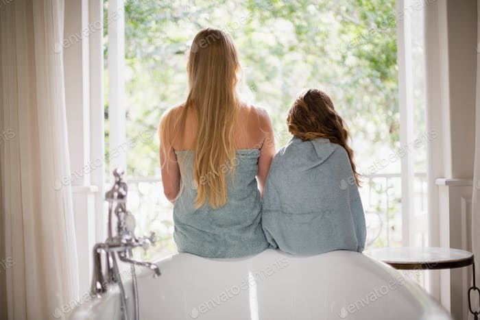 Rear view of mother and daughter sitting on bathtub