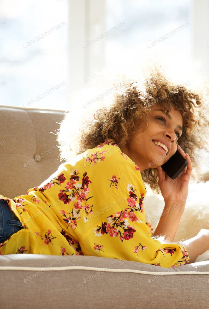 happy young woman lying on couch at home talking with mobile phone