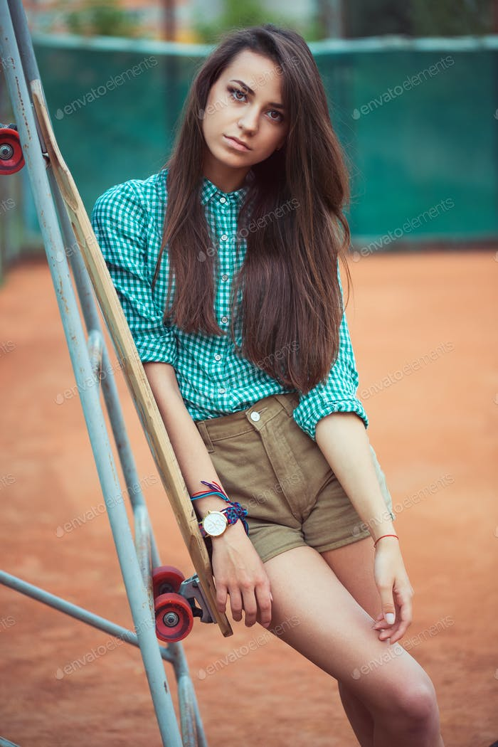 Beautiful young girl with longboard standing on the tennis court