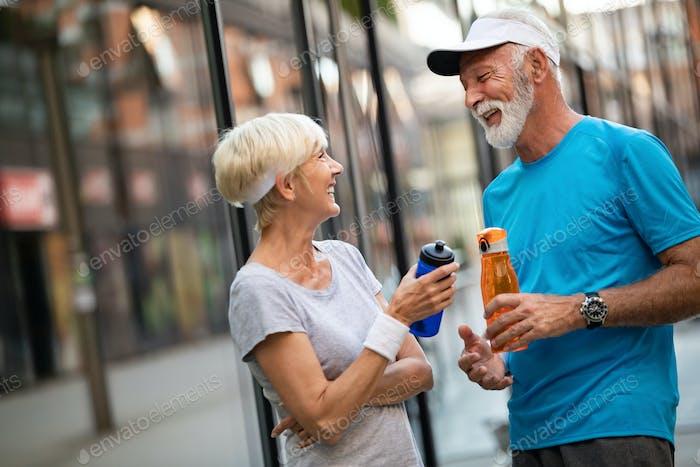 Fitness, Sport und Lifestyle-Konzept - glückliches reifes Paar in Sportbekleidung im Freien