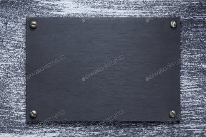 wooden nameplate or wall sign at wooden background