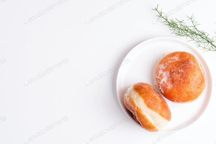 Homemade baked donut on a white ceramic plate on a light grey background. Flat lay