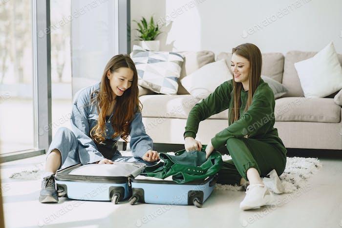 Frauen bereiten Reisekoffer zu Hause vor