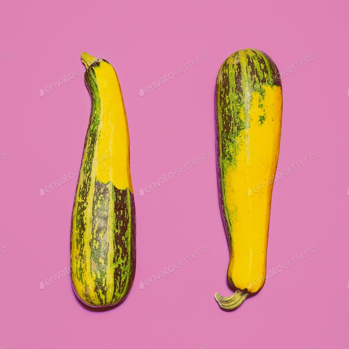 Two zucchini on bright pink background. design Photo