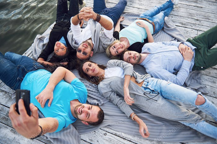 Group of beautiful young people who do Selfies lying on the pier, the best friends of girls and boys
