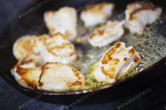 Close up of scallops in a frying pan.