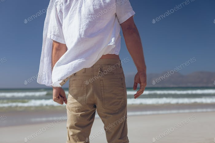 Mid section of young Caucasian man standing at beach on a sunny day