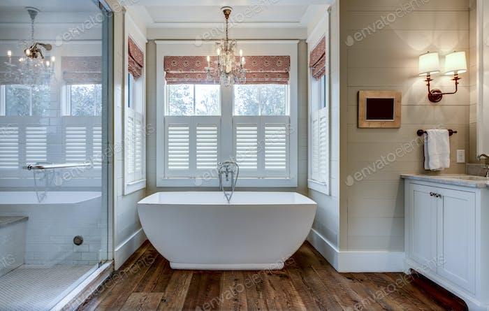 Cuarto de  baño de gama alta con gran bañera blanca y revestimiento de shiplap.