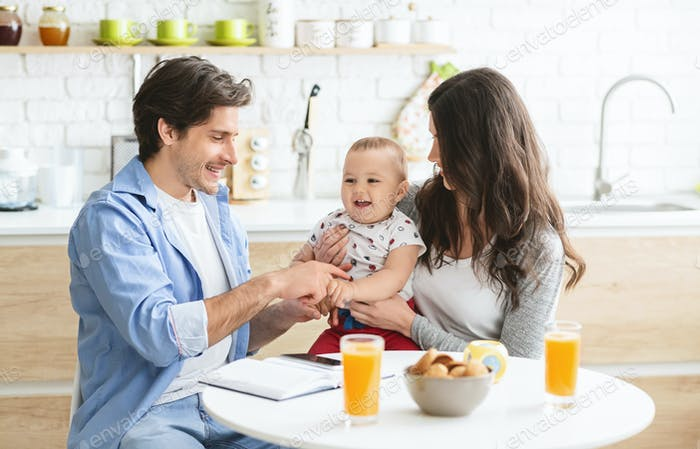 Millennial parents working at kitchen with baby