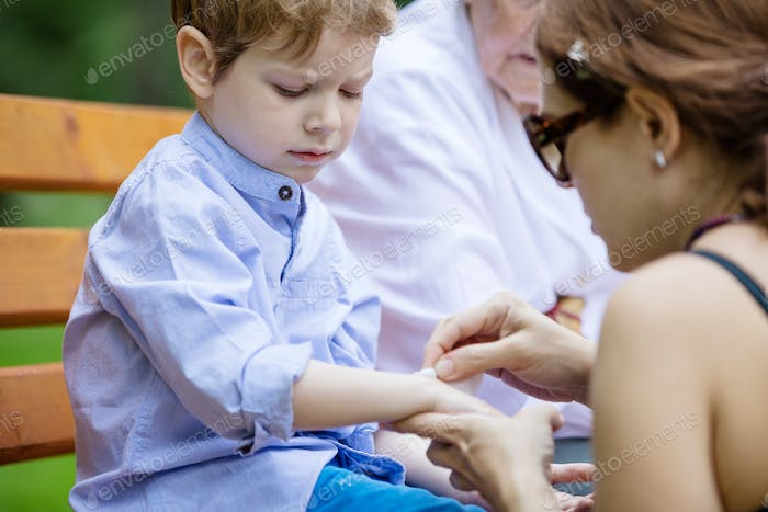 other applying band aid on scratch on son's arm outdoors