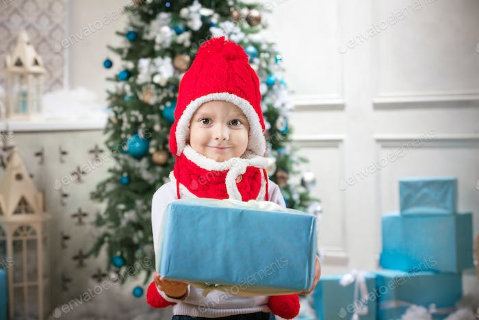 Cute little boy holding a gift against Christmas tree in background