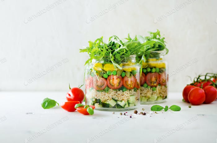 Healthy salad jar with quinoa and vegetables, cherry tomatoes, cucumber, ruccola. Raw vegetarian