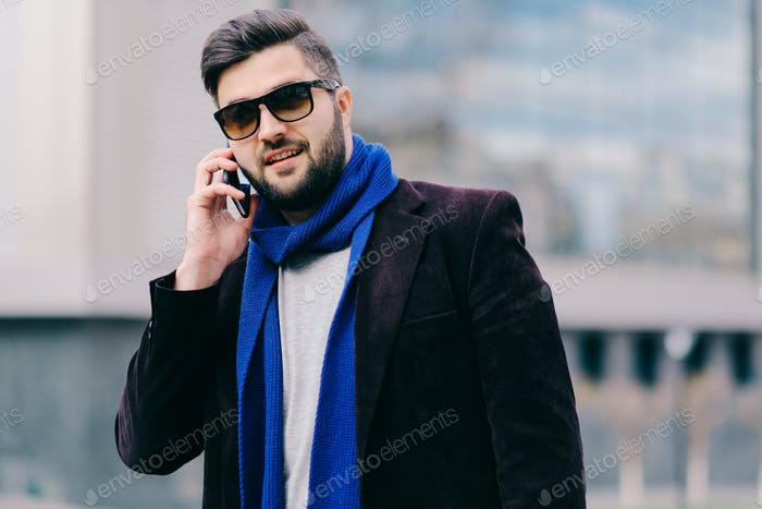 Young man with mobile phone in the street