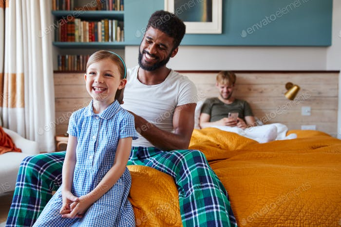 Same Sex Male Couple At Home Getting Daughter Ready For School Plaiting Her Hair