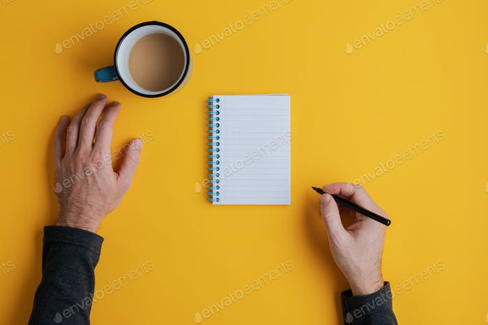 Top view of a man ready to write in his blank note pad