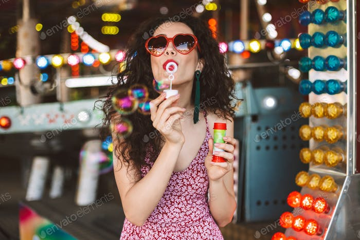 Beautiful lady in heart sunglasses and dress standing and blowing bubbles in amusement park