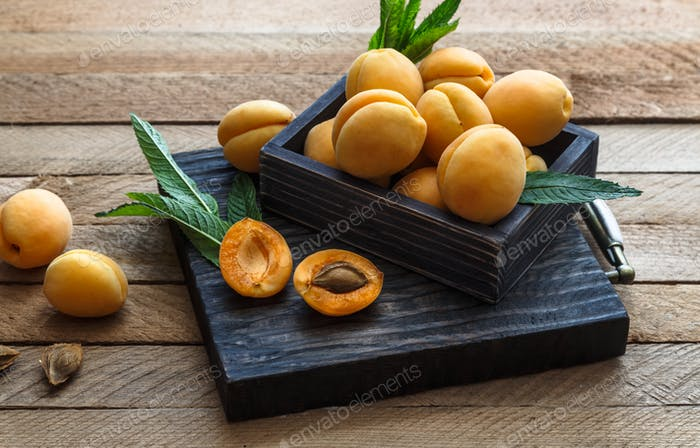 Delicious ripe apricots in a wooden box on the table close-up.