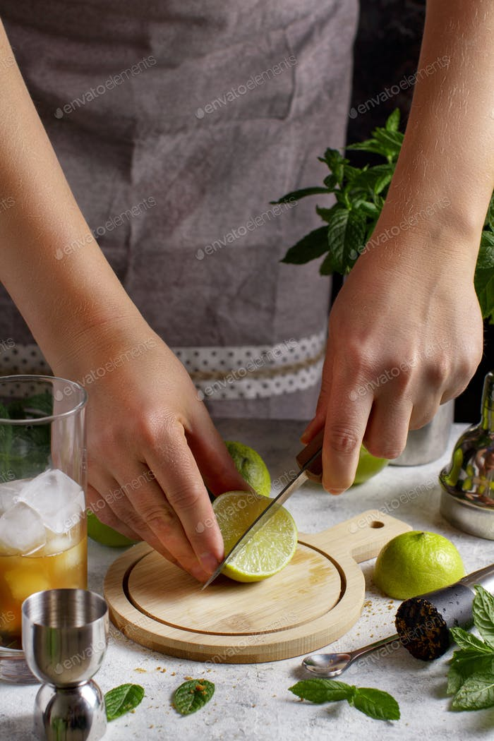 Hands cut fresh lime for Mojito cocktail
