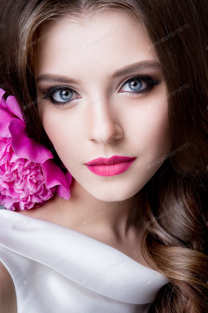 Close-up studio portrait of beautiful woman with bright make-up