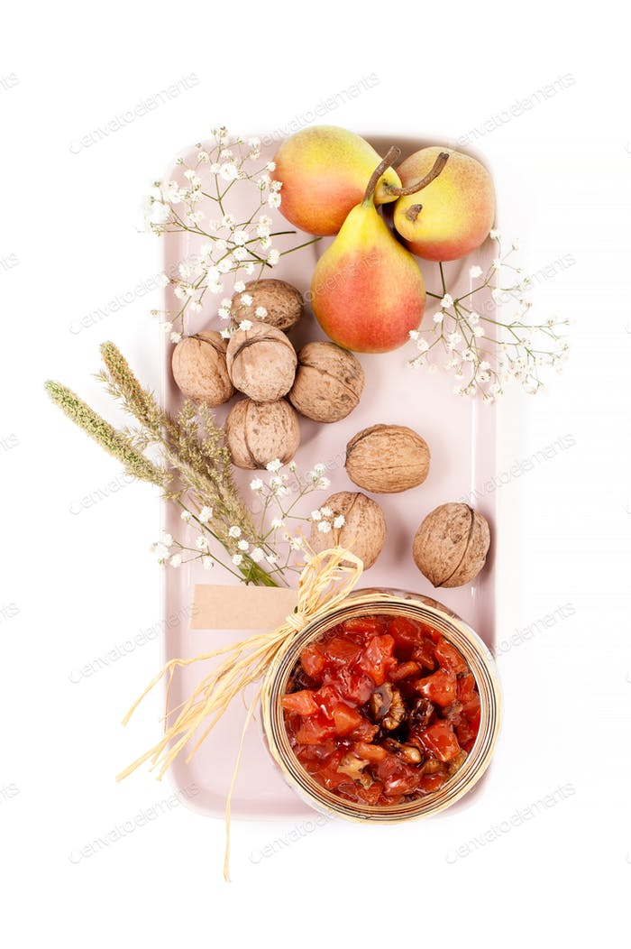 Pear jam, pears and walnuts are served on a light pink tray on a
