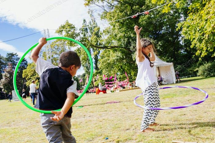Girl (6-7) and boy playing with hula hoops