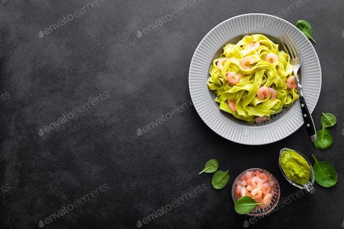 Gekochte Fettuccine Pasta mit frischem Spinatpesto und Garnelen auf schwarzem Hintergrund. Italienische Küche