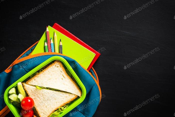 Zurück zum Schulkonzept. Lunchbox, Schreibwaren und Rucksack