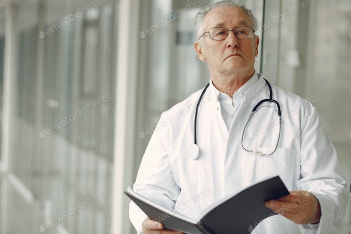 Old doctor in a uniform standing at the hall