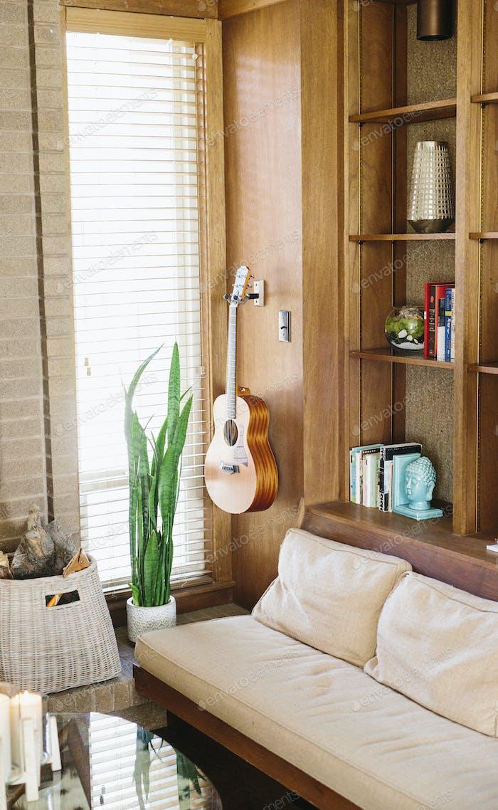 Innenansicht eines Wohnzimmers mit Sofa, Couchtisch, Bücherregal und Akustikgitarre