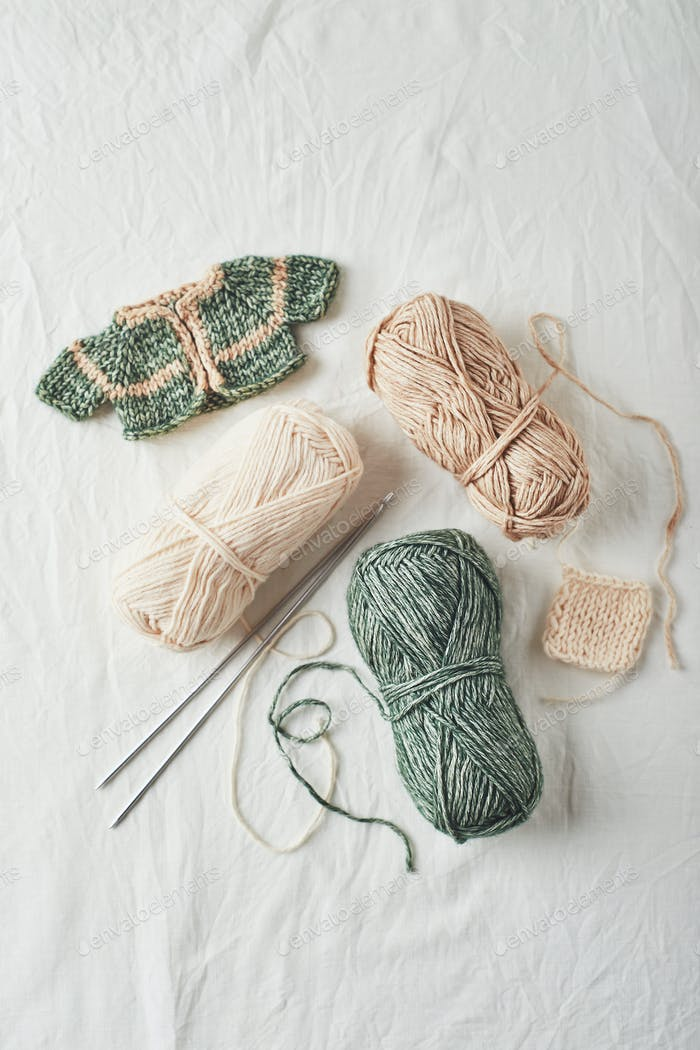 Handmade knitted small sweaters and threads on light background.