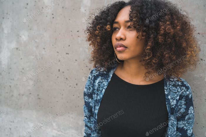 Afro-american woman against grey wall.