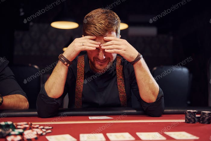 Elegant young man sits in casino and feels bad because loses poker game
