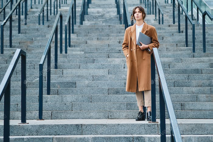 Young attractive businesswoman in coat with laptop thoughtfully looking away outdoor