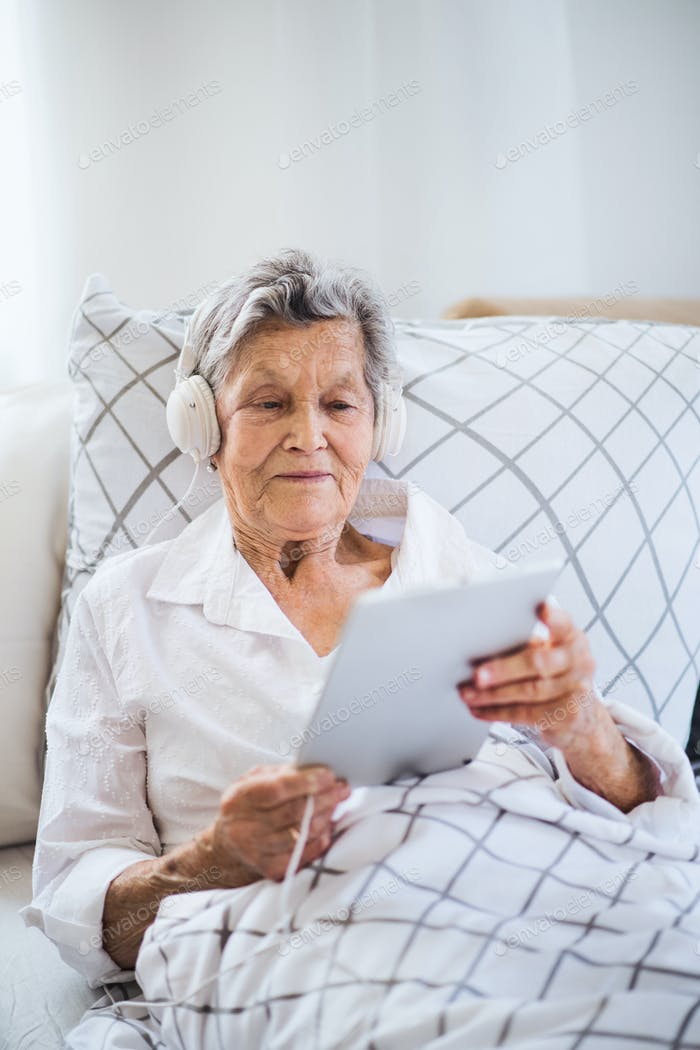 Sick senior woman with headphones and tablet lying in bed at home or in hospital.