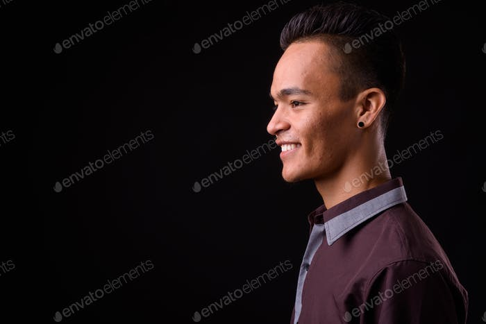 Closeup profile view of young handsome Indian businessman