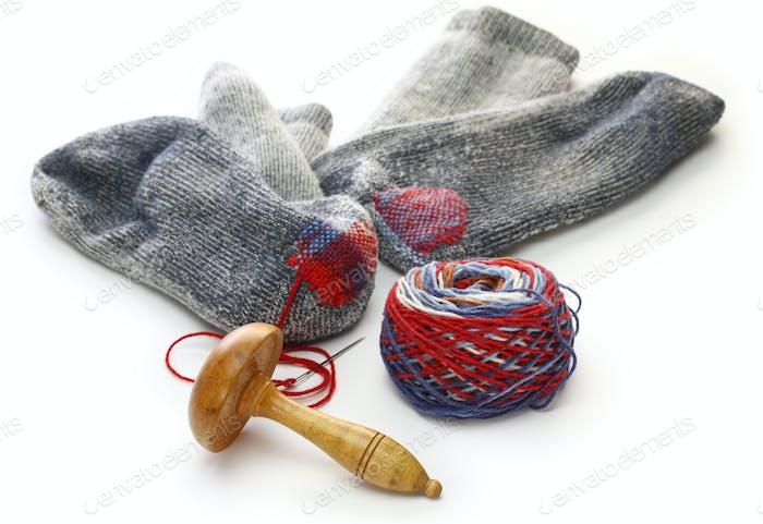 darning socks, repairing holes in socks on white background