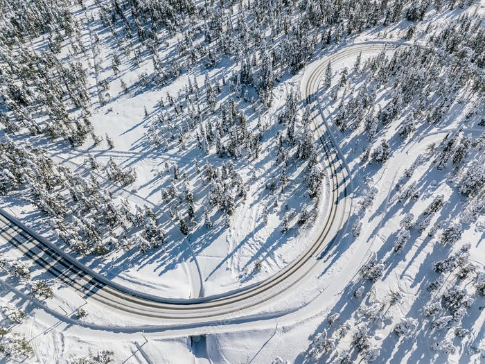 Top aerial view of snowy and frozen winter road.