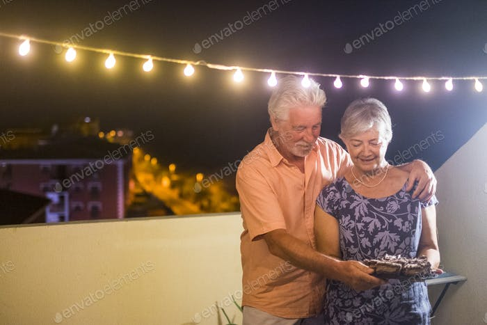 Happy senior adult couple with a chocolate cake